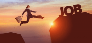 "A woman wearing a formal business suit and carrying a work bag is jumping from one rock to another rock that is holding up letters that spell ""job."""