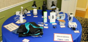 "Various assistive technologies are displayed on a round table covered by a blue tablecloth. One sign on the left side of the table reads ""Telepresence Devices,"" and a second sign on the right reads ""Wearables."" Some of the technologies include fitness and health trackers, specialized clothing, and lamps and door locks controlled by Alexa and Echo devices."