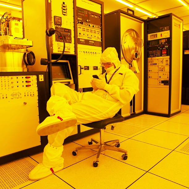 A researcher looking at their cell phone in a laboratory.