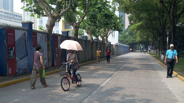 A women in Shanghai cycles down the street, holding an umbrella to shield herself from the sun
