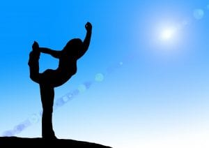 Silhouette of woman doing yoga on blue sky background