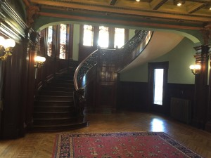 The Grand stair-case with the painted glass windows behind it.