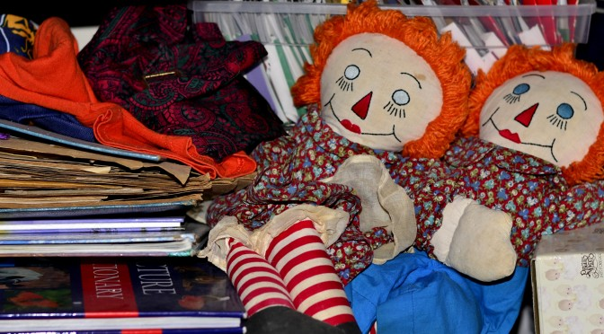 An image of old Raggedy Ann and Andy dolls, with other stored items such as books and old clothing.