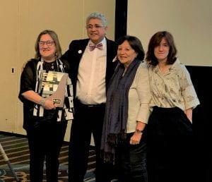 Dr. Vélez Vega and Dr. Pietro Aparicio pose with Dr. Vélez Vega's family after the ceremony
