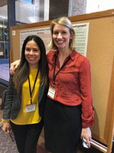 Left: Dr. Gredia Huerta-Montanez and Dr. Emily Zimmerman pose in front of Dr. Zimmerman's poster.