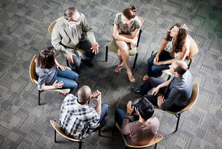 Group of students sitting in a circle in a discussion