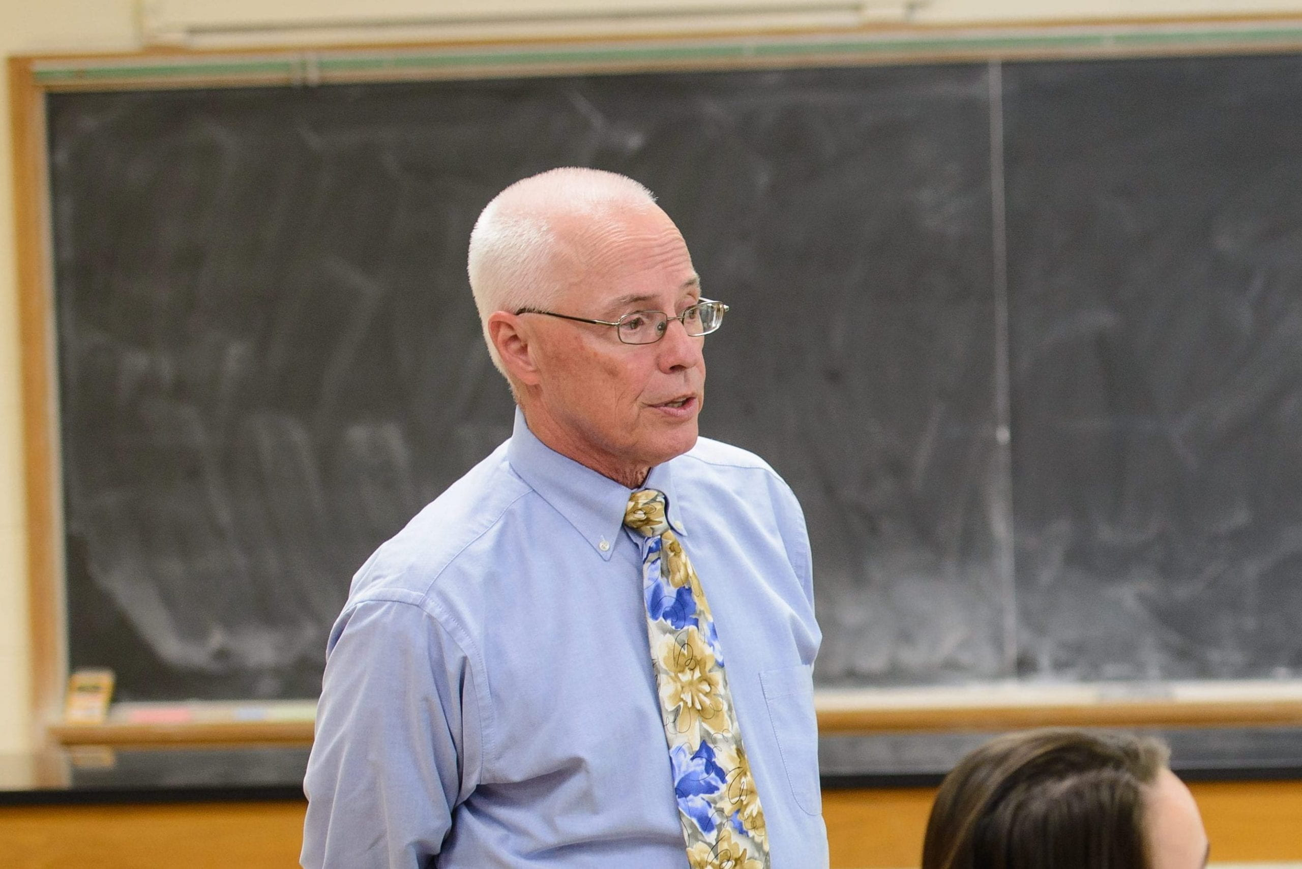 Image of Carl Caster, Science professor, teaching.  He is seen from waist up, wearing glasses, sporting a white hair crew cut, a light blue button up shirt, with a brightly colored blue and gold flower tie.  Blackboard in background.