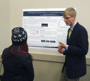 Student presenting research in a poster session