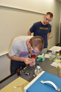 Ace Manning (SEU undergraduate) prepares an ozonesonde for flight while Physics Professor Paul Walter supervises.