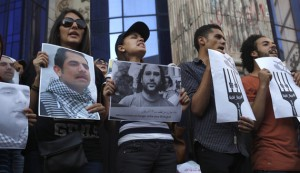 Protesters hold pictures during a protest in support of imprisoned activists who are in a hunger strike at prison, in front of the Press Syndicate, in Cairo