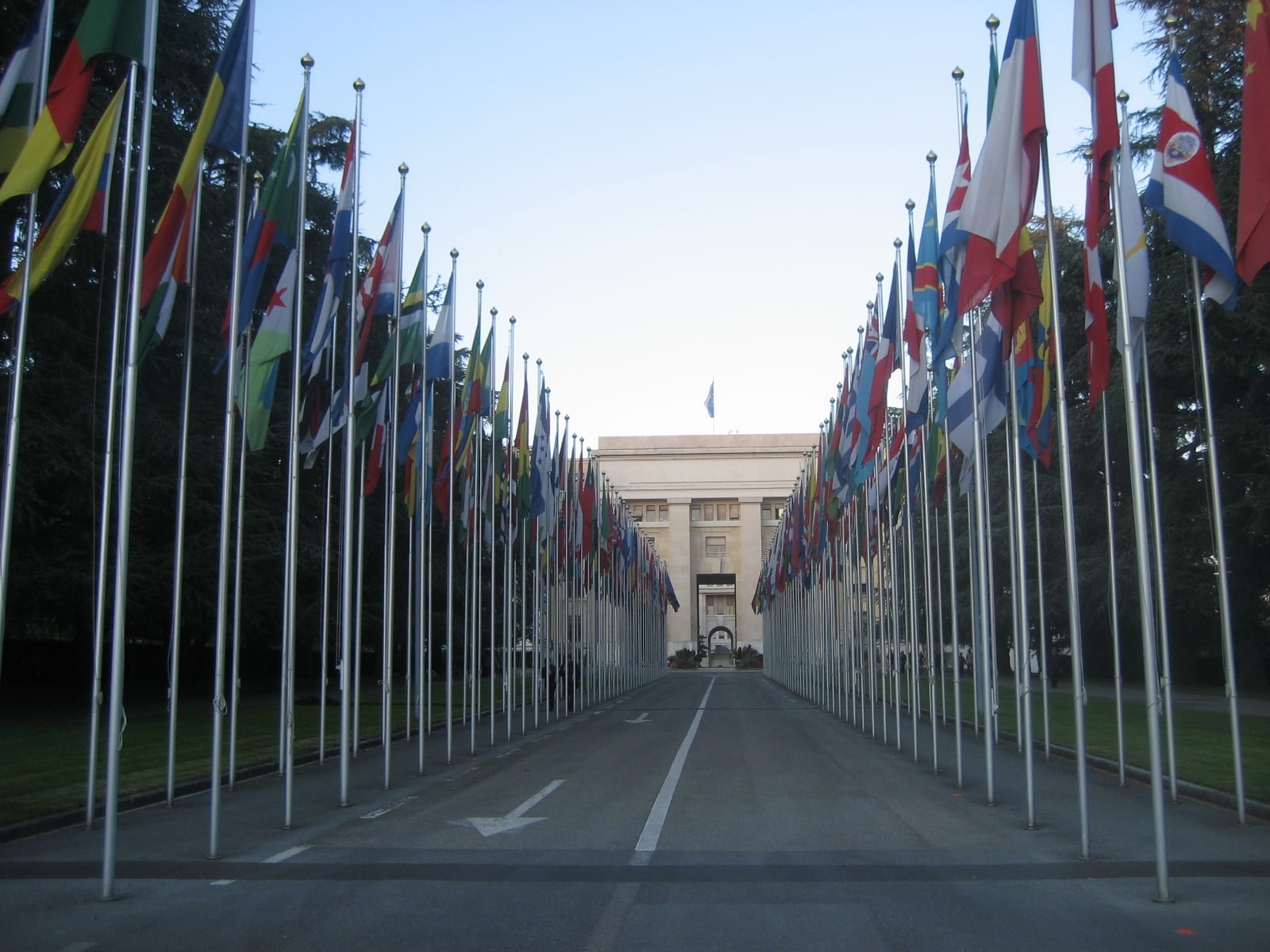 Picture of flags and street leading up to the United Nations Palais des Nations in Geneva.