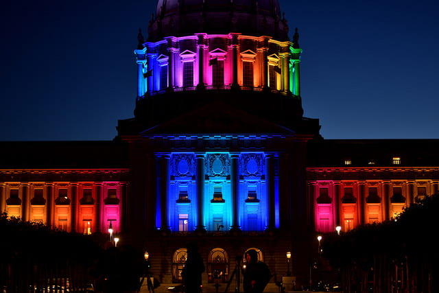 a picture of a city hall building, lighted with rainbow colored lights in honor of gay pride