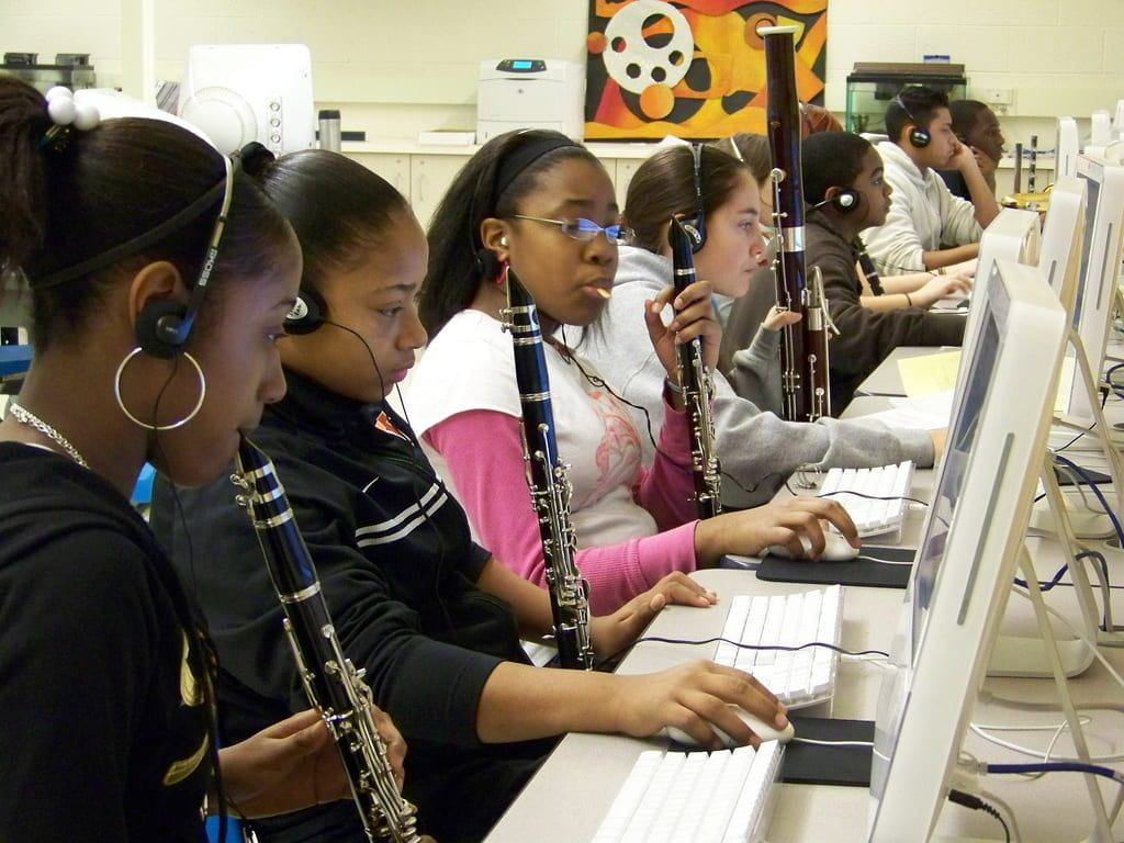 a picture of girls playing clarinets while in a computer lab