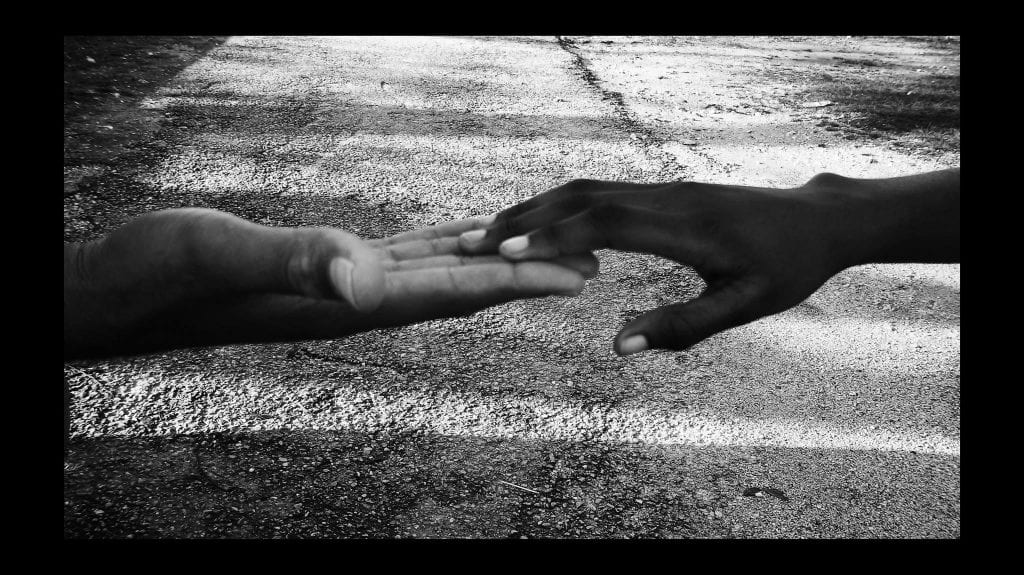 a picture of two people touching hands in unity