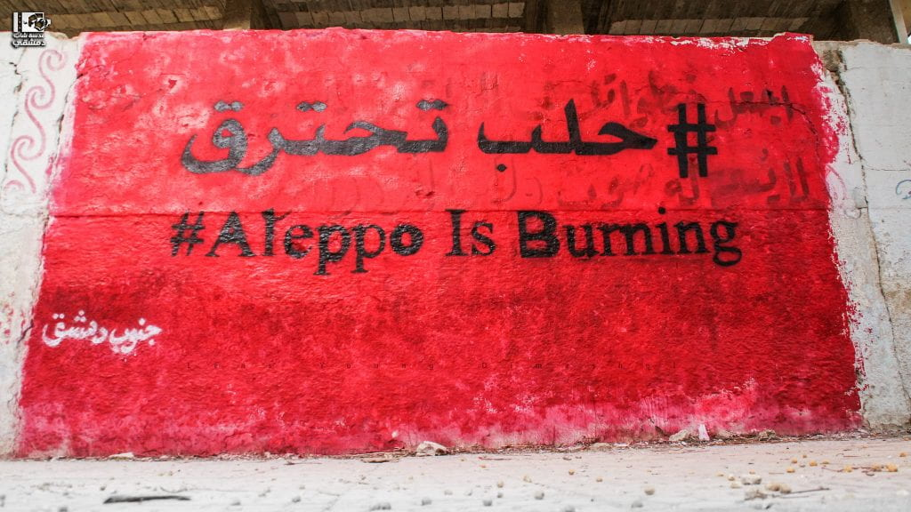 "Photo of a sign reading: ""#Aleppo Is Burning"