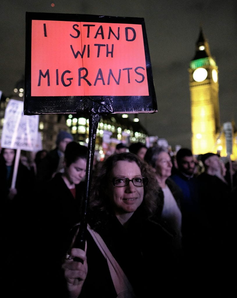 "A woman at a protest in London holds a sign saying, ""I stand with migrants."""