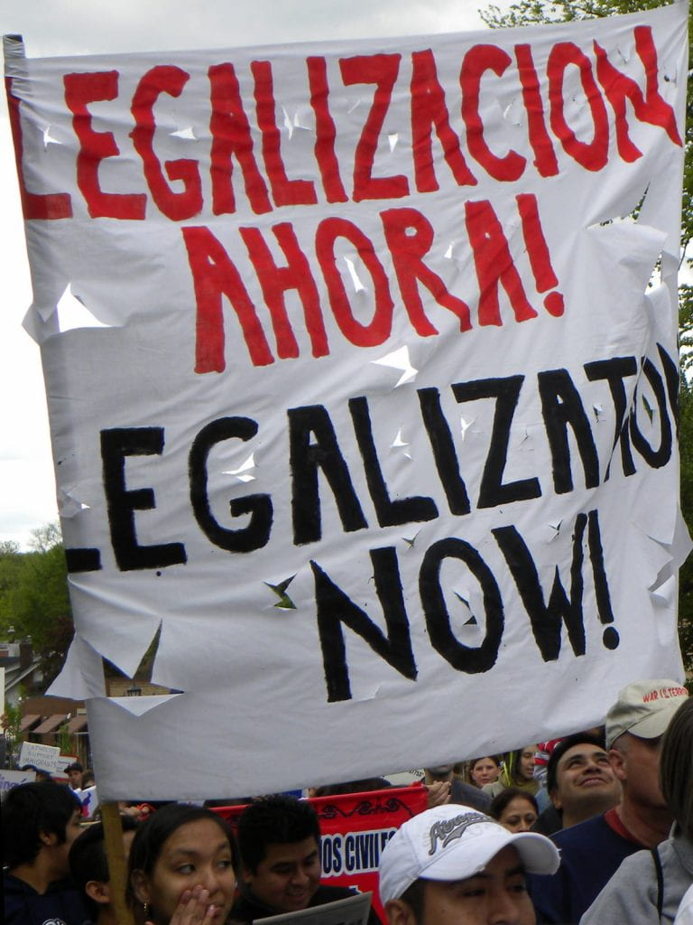 "A ripped banner that says, ""Legalizacion Ahora!"" and then ""Legalization Now!"""