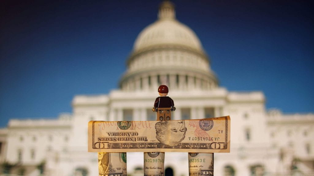 a picture of a toy standing on a pile of money