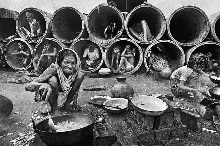Refugees sit in cement pipes while other refugees cook.