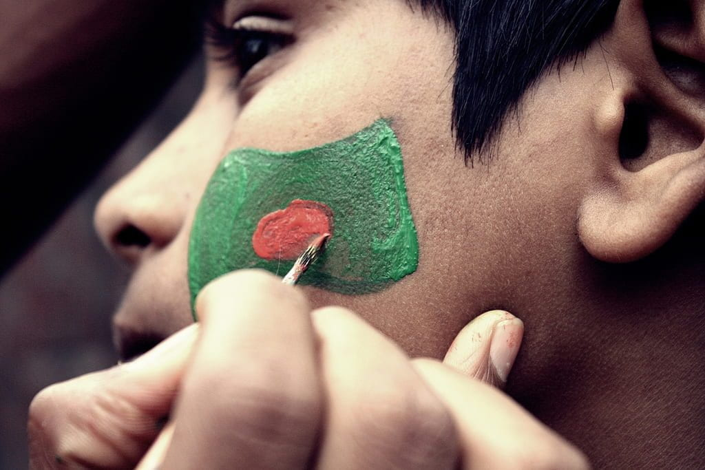 A boy has the flag of Bangladesh painted on his face.