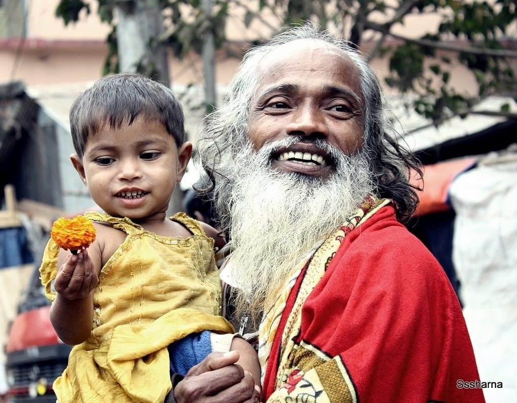 An old man with a beard and child sitting on his shoulder in a yellow dress celebrate 40 years of Bangladesh Independence.