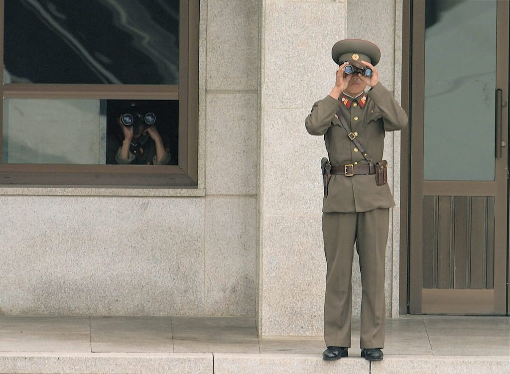 a picture of two North Korean soldiers looking through binoculars towards the South
