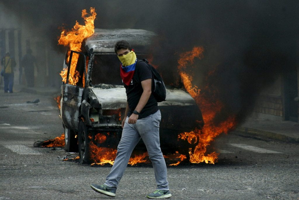a picture of a man walking in front of a burning car during a Venezuelan protest