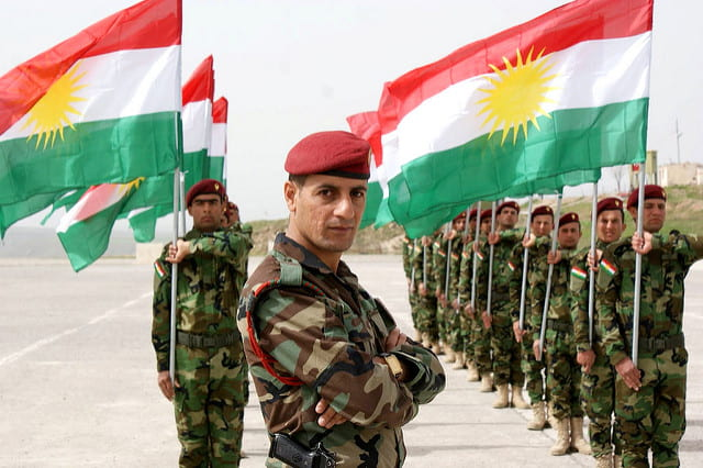Kurdish soldiers salute the Kurdish flag.