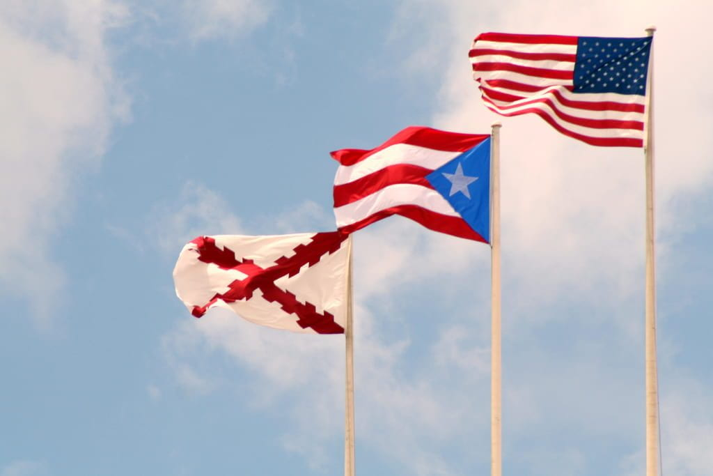 The American flag, Puerto Rican flag, and Spanish flag are shown flying in front of a blue sky.