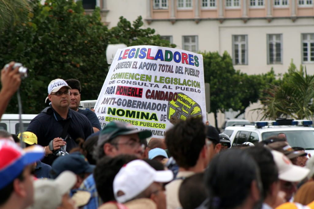 Puerto Rican protesters hold a sign protesting government corruption.