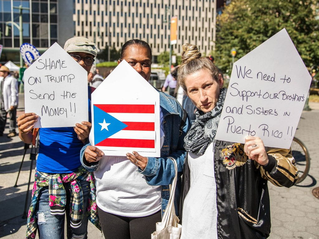 Three people hold signs at a protest supporting Puerto Rico.