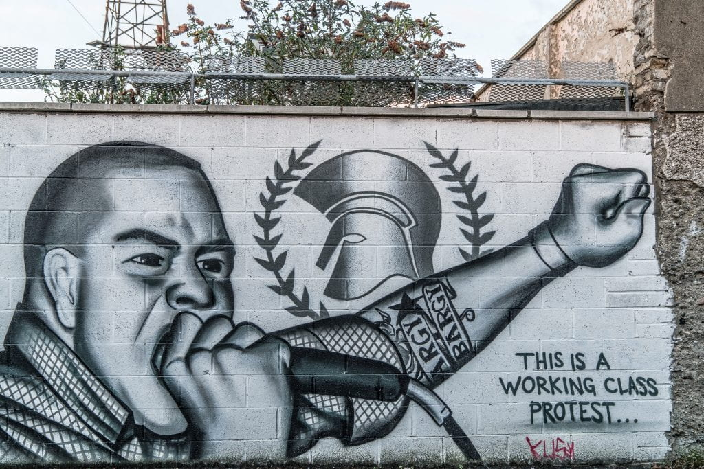 "White wall with black and white graffiti of a man holding a microphone with fist in the air. Text at the bottom of the graffiti says, ""This is a working class protest..."""
