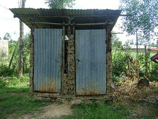 a picture of a traditional pit latrine, which looks like a very small building with a tin roof and two tin doors