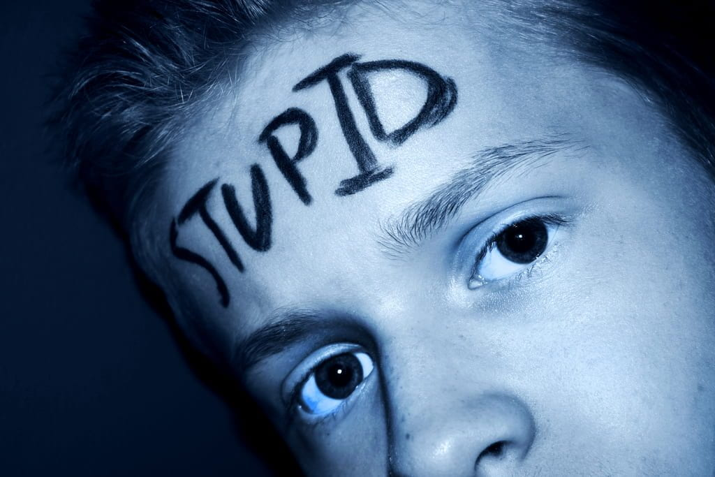 a picture of a boy with 'stupid' written across his forehead