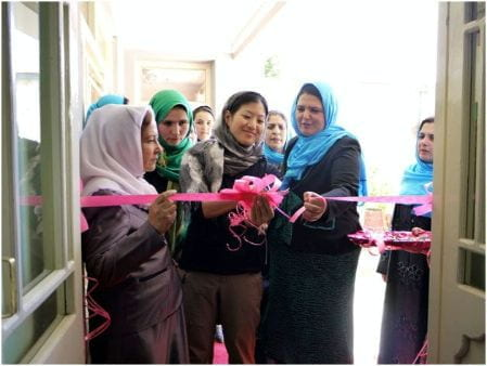 A group of hijabi women cut a ribbon to open the new shelter.