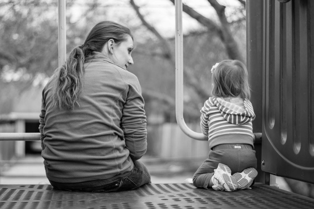 A woman sits on a playground next to her young daughter.
