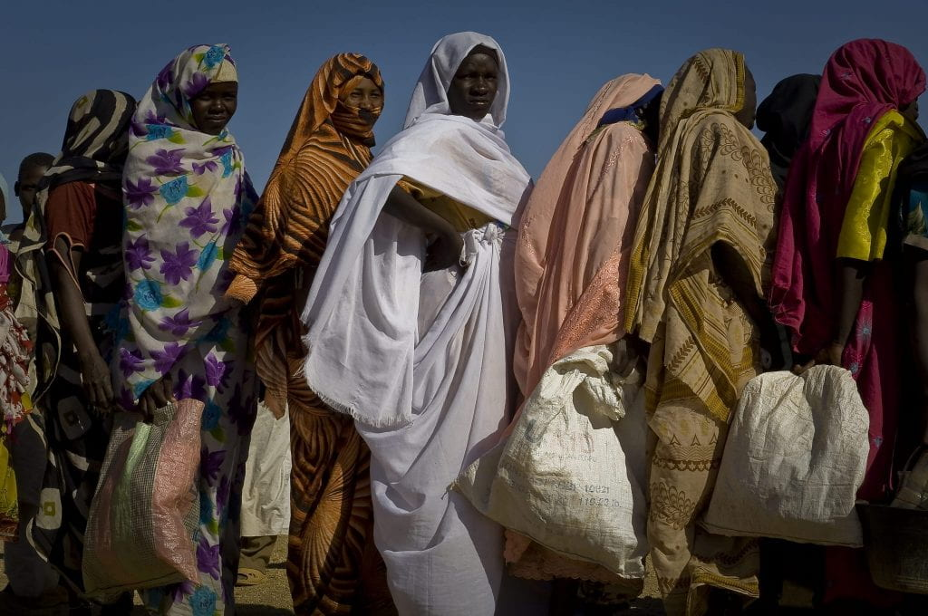 A group of refugee women stand in a line.