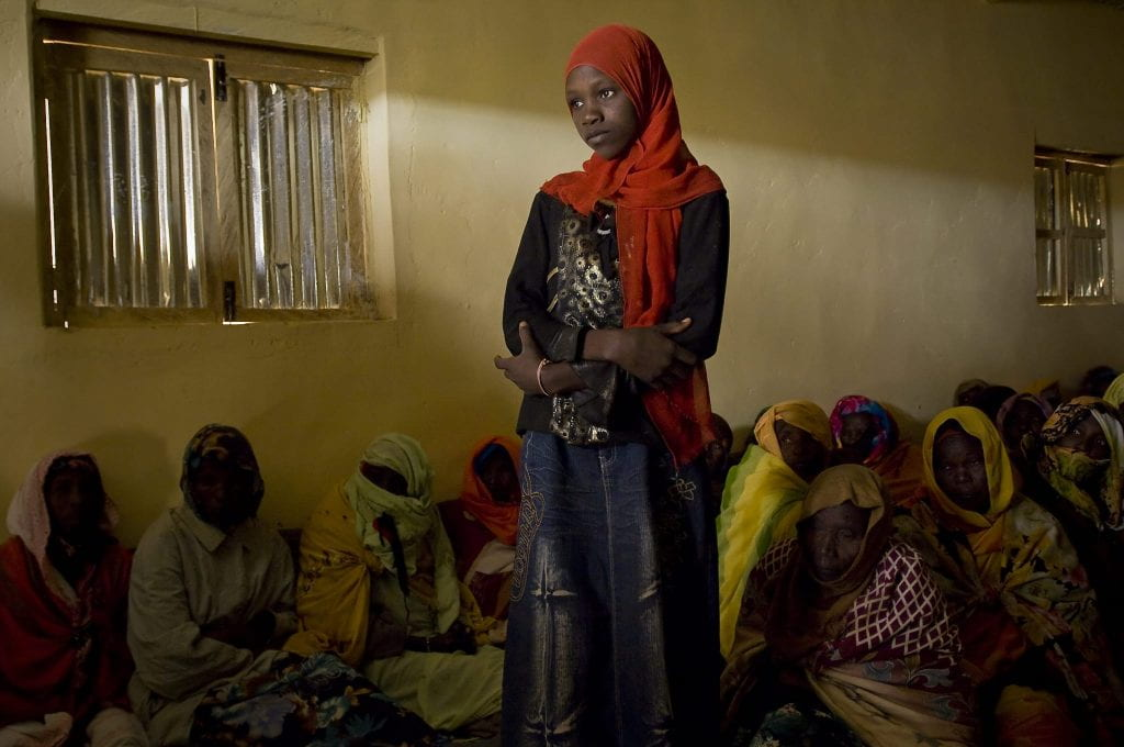 A refugee woman in a bright red hijab stands in a dark room with other women seated on the floor behind her.