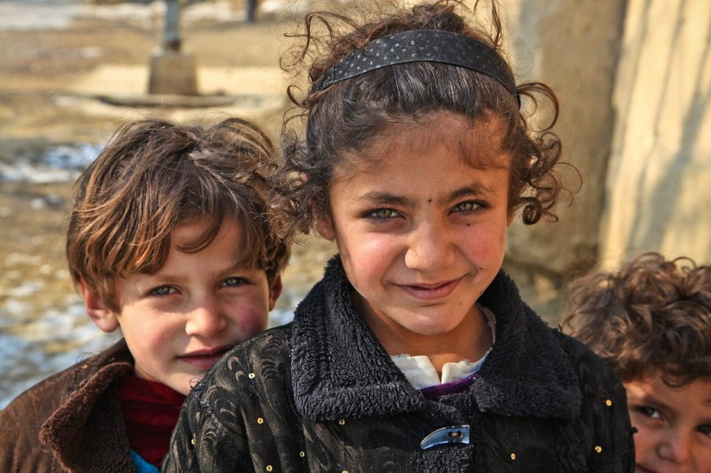 Three curly haired Afghan kids look up to the camera