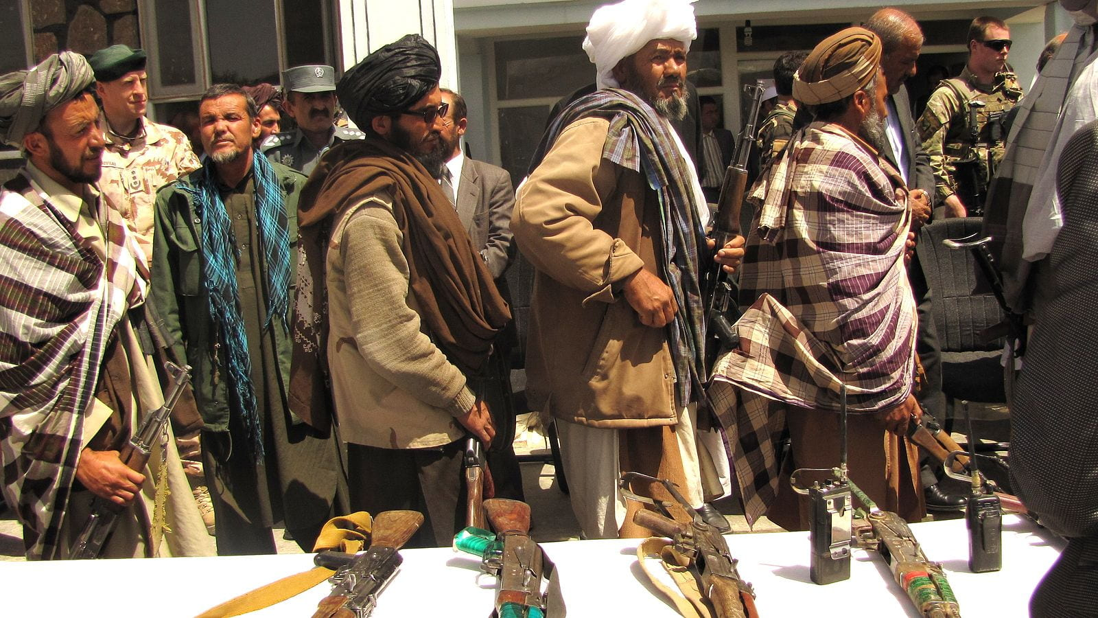 A line of Taliban soldiers stand beside a table handing in their weapons
