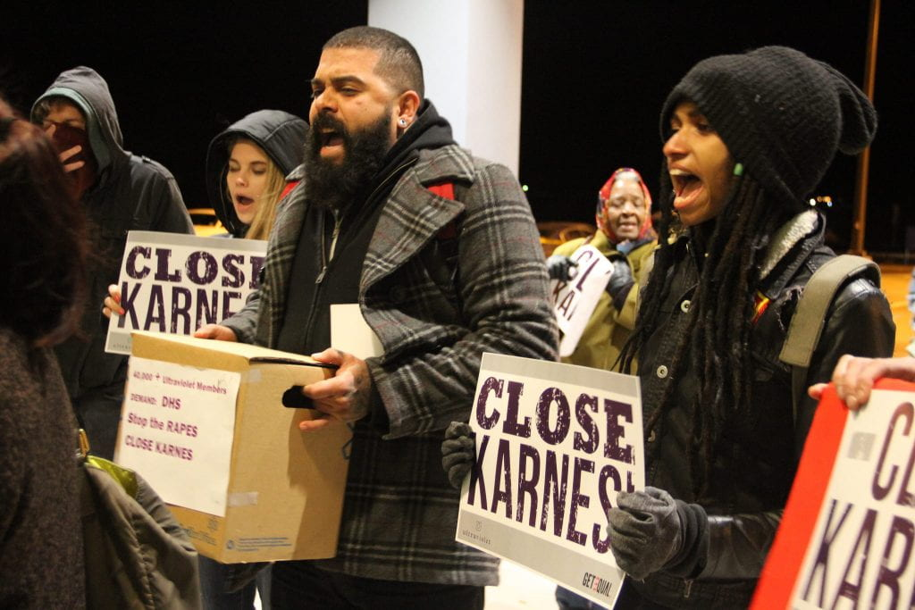 "A crowd of people appear to be yelling as they hold signs that say ""Close Karnes."""