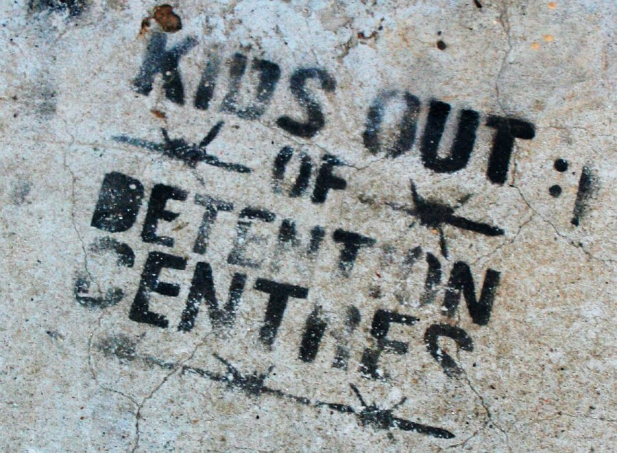 """Kids Out of Detention Centers"" is stamped onto concrete in black ink with barbed wires surrounding the text."