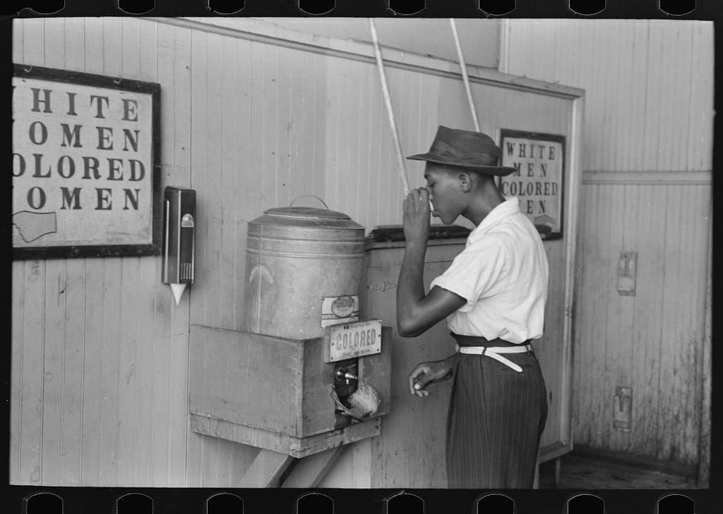 "Negro drinking at ""Colored"" water cooler in streetcar terminal, Oklahoma City, Oklahoma (LOC)"