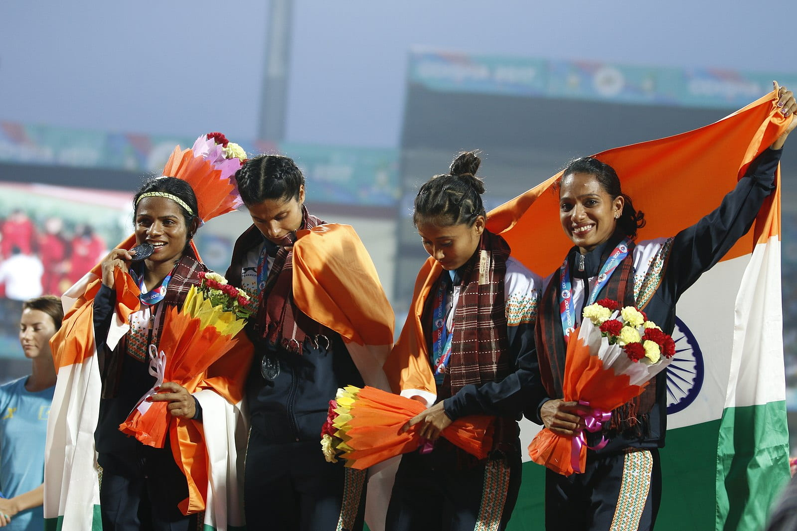 Dutee Chand bites her medal on the left while standing with her three teammates.