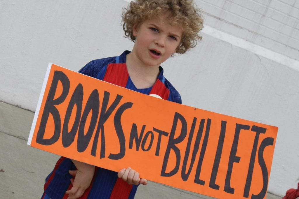 "a picture of a boy holding a sign which reads ""books not bullets"" during the March for Our Lives"