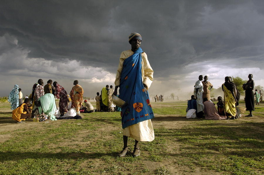 An elderly Sudanese womangets ready to receive her ration of emergency food aid.