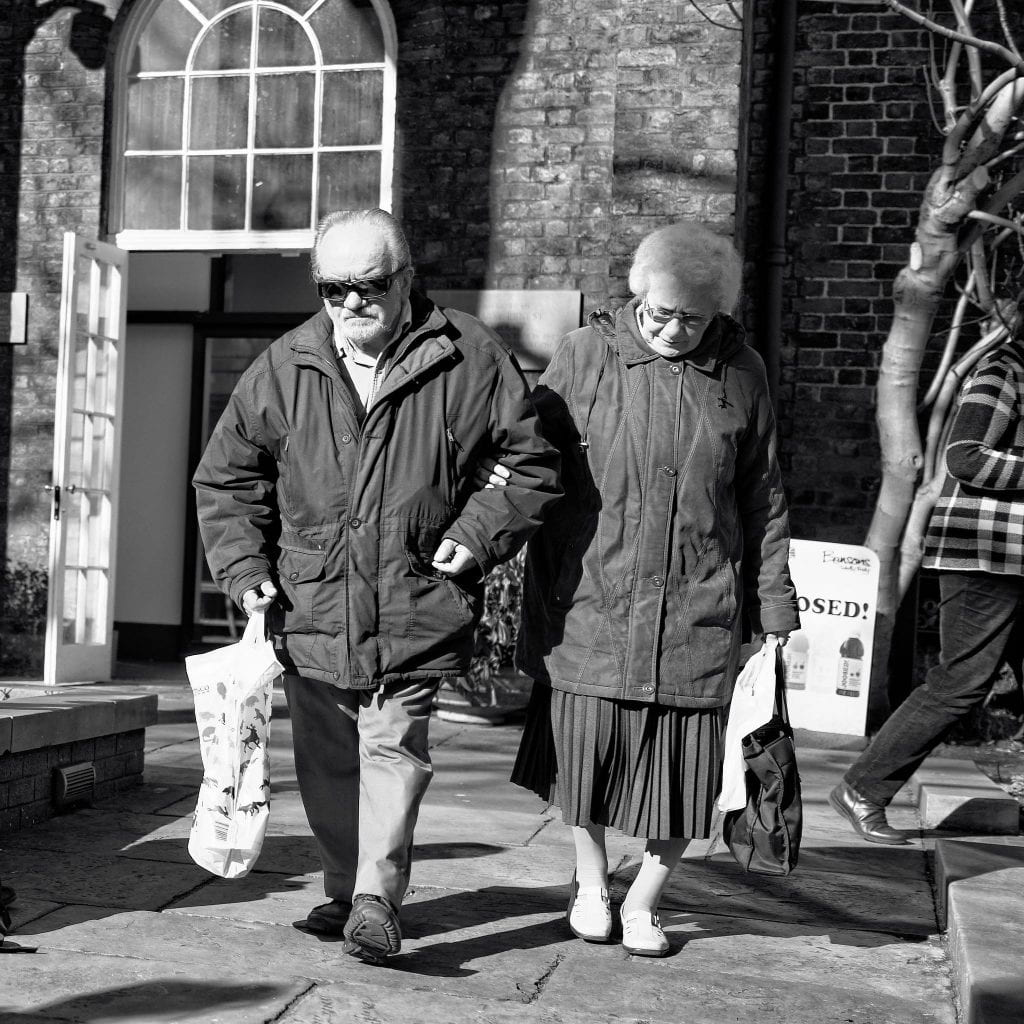 An older couple links arms as they carry bags and walk together.