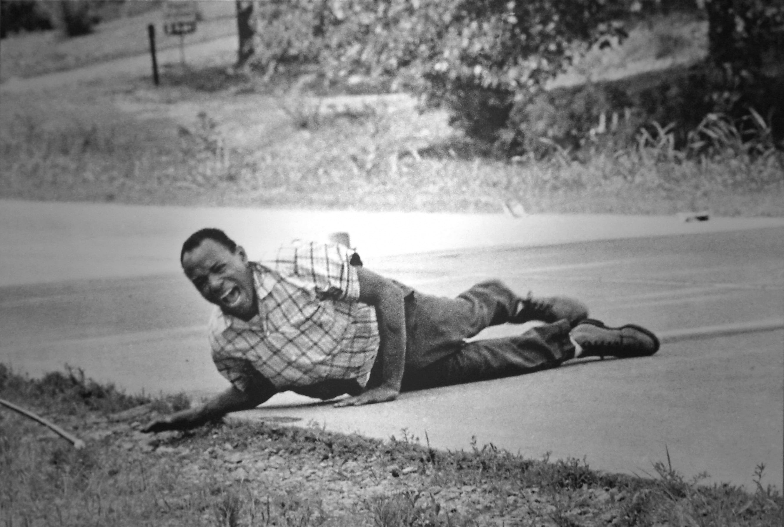 After being shot, a black American man sprawls on the ground
