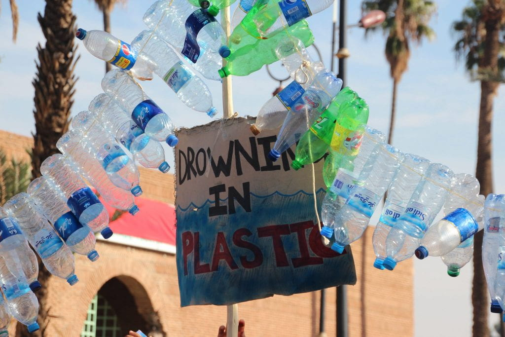 "A sign that says ""Drowning in Plastic"" is hung on a fence surrounded by a string of empty plastic water bottles."