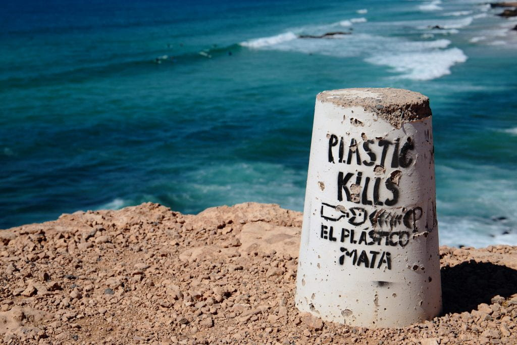 "A concrete cylinder sits on the right of the shot, in front of ocean waves. The cylinder has ""plastic kills! El plastico mata !"""
